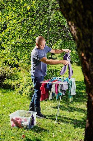 skinhead - Finland, Paijat-Hame, Heinola, Man hanging laundry on drying rack Stock Photo - Premium Royalty-Free, Code: 6126-08636522