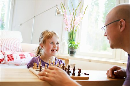 skinhead - Father learning daughter (6-7) play chess Stock Photo - Premium Royalty-Free, Code: 6126-08636537