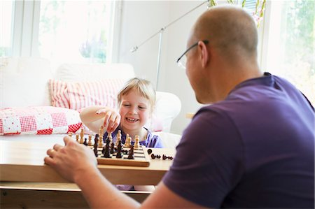 skinhead - Father learning daughter (6-7) play chess Stock Photo - Premium Royalty-Free, Code: 6126-08636536