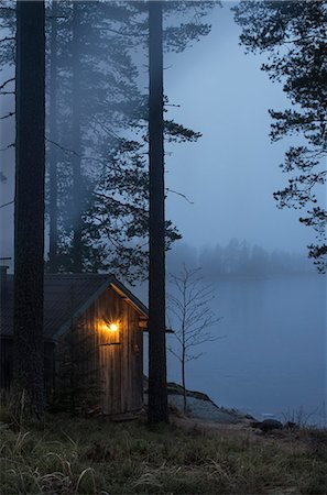 Finland, Pirkanmaa, Ruovesi, Illuminated wooden cottage on foggy day Stock Photo - Premium Royalty-Free, Code: 6126-08636774