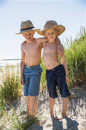 preteen boy shirtless - Sweden, Gotland, Shirtless boys (6-7, 8-9) in straw hats standing on sand dune at seashore Stock Photo - Premium Royalty-Free, Code: 6126-08781180
