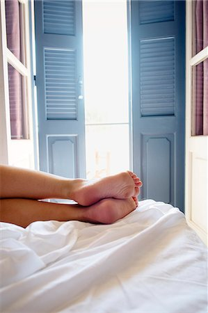 south european - Greece, Kalymnos, Female legs on bed in sunny bedroom Stock Photo - Premium Royalty-Free, Code: 6126-08781130