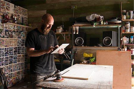 skinhead - Israel, Man with digital tablet in workshop Stock Photo - Premium Royalty-Free, Code: 6126-08781358