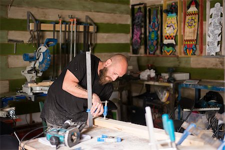 skinhead - Israel, Man working with piece of wood in workshop Stock Photo - Premium Royalty-Free, Code: 6126-08781360