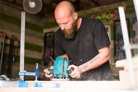 skinhead - Israel, Man cutting wood in workshop Stock Photo - Premium Royalty-Free, Code: 6126-08781361