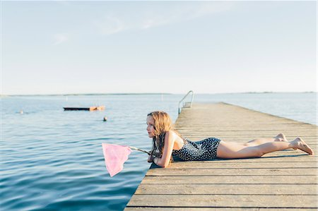 Sweden, Blekinge, Karlskrona, Salto, Girl (10-11) lying on pier and fishing Stock Photo - Premium Royalty-Free, Code: 6126-08781448