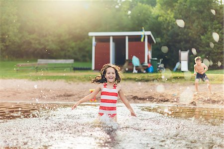 Sweden, Smaland, Mortfors, Kappemalagol, Girl (8-9) splashing water and boy (6-7) standing on ground Stock Photo - Premium Royalty-Free, Code: 6126-08781422