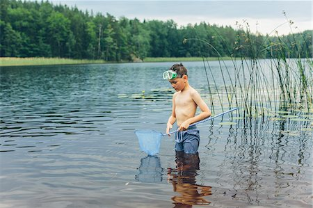Sweden, Smaland, Mortfors, Kappemalagol, Boy (8-9-) wading and fishing Stock Photo - Premium Royalty-Free, Code: 6126-08781435