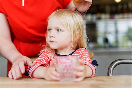 Mother standing behind daughter holding drinking glass at cafe table Stock Photo - Premium Royalty-Free, Code: 6127-08666289