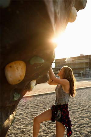sports - Side view of teenage girl climbing up artificial rock Stock Photo - Premium Royalty-Free, Code: 6127-08666375