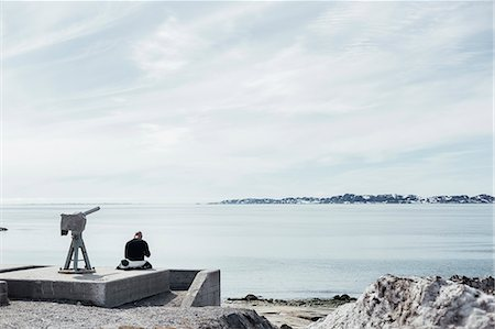 Rear view of man sitting by telescope overlooking sea against sky Stock Photo - Premium Royalty-Free, Code: 6127-08666694