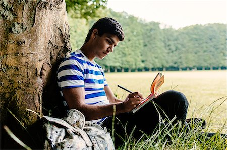studying (all students) - Man writing in book while studying at park Stock Photo - Premium Royalty-Free, Code: 6127-08666836