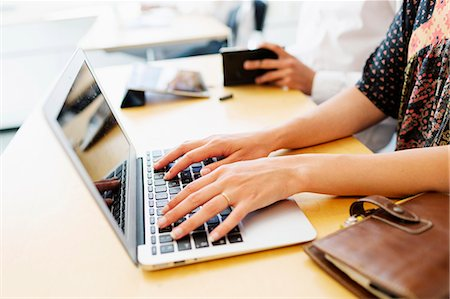 female hand - Cropped image of female student using laptop at desk in classroom Stock Photo - Premium Royalty-Free, Code: 6127-08666915