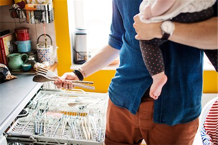 Midsection of man emptying dishwasher while carrying baby in kitchen Stock Photo - Premium Royalty-Free, Code: 6127-08667067