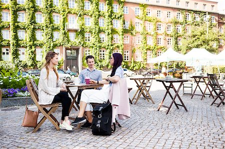 square - Friends discussing at sidewalk cafe in town square Stock Photo - Premium Royalty-Free, Code: 6127-08667104