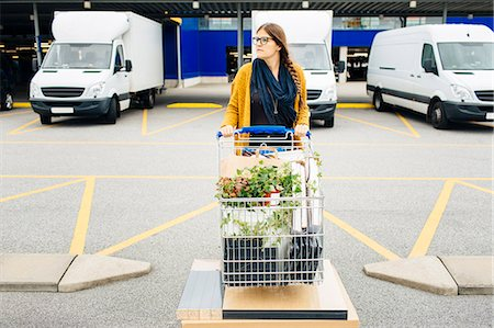Young woman pushing trolley full of purchases in car park Stock Photo - Premium Royalty-Free, Code: 6127-08667378