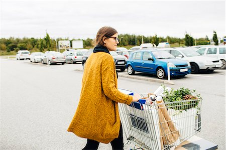 Side view of young woman pushing trolley full of purchases towards car park Stock Photo - Premium Royalty-Free, Code: 6127-08667379
