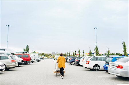 person walking on parking lot - Rear view of young woman pushing shopping cart in car park Stock Photo - Premium Royalty-Free, Code: 6127-08667380