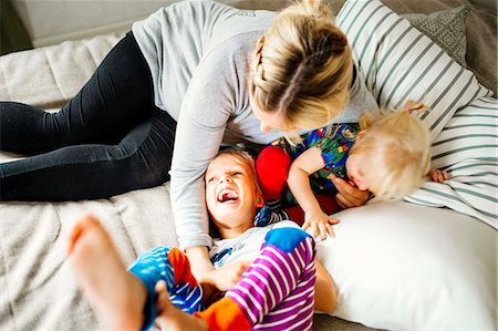 High angle view of mother playing with children in bed Stock Photo - Premium Royalty-Free, Code: 6127-08687749