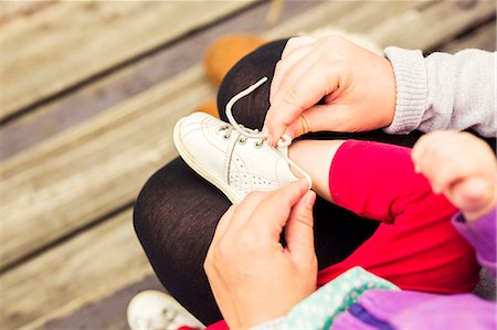 family shoes - Low section of mother putting shoes on daughter outdoors Stock Photo - Premium Royalty-Free, Code: 6127-08687767
