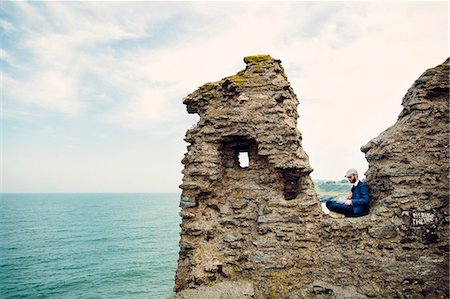 Man sitting on cliff by sea against sky Stock Photo - Premium Royalty-Free, Code: 6127-08687722