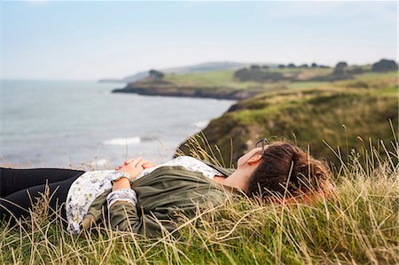 friluftsliv - Side view of woman lying on grassy hill by sea Stock Photo - Premium Royalty-Free, Code: 6127-08687737