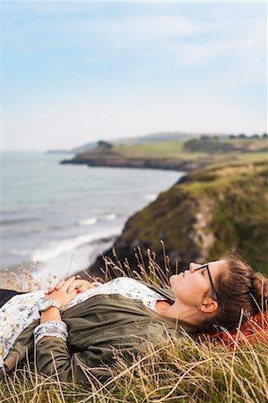 friluftsliv - Side view of woman sleeping on grassy hill by sea Stock Photo - Premium Royalty-Free, Code: 6127-08687736