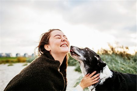 Cheerful young woman playing with dog on beach against sky Stock Photo - Premium Royalty-Free, Code: 6127-08687856