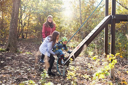 Mother watching children climbing obstacle wall in forest Stock Photo - Premium Royalty-Free, Code: 6127-08688087