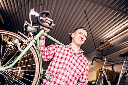 Low angle view of happy mechanic carrying bicycle in shop Stock Photo - Premium Royalty-Free, Code: 6127-08688189