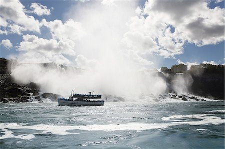Ferry sailing by Niagara Falls against cloudy sky Stock Photo - Premium Royalty-Free, Code: 6127-08688124
