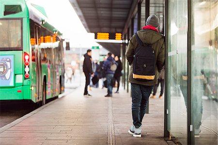 Rear view of man waiting at bus stop Stock Photo - Premium Royalty-Free, Code: 6127-08688130