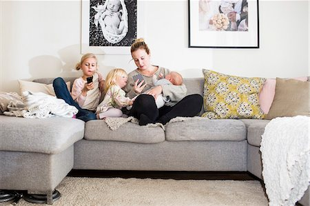 Girls sitting by mother on sofa at home Stock Photo - Premium Royalty-Free, Code: 6127-08688272