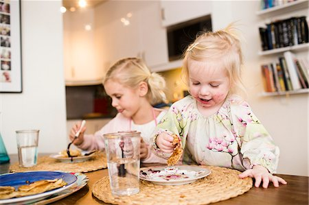 Cute girls eating pancakes on table at home Stock Photo - Premium Royalty-Free, Code: 6127-08688281