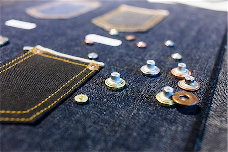 Buttons on denim fabric in factory Stock Photo - Premium Royalty-Free, Code: 6127-08689200
