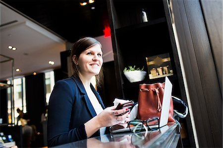 restaurant new york manhattan - Smiling businesswoman with smartphone and laptop at coffee shop Stock Photo - Premium Royalty-Free, Code: 6127-08704260