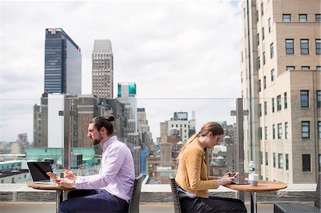 restaurant new york manhattan - Side view of business people working while sitting at rooftop restaurant by window Stock Photo - Premium Royalty-Free, Code: 6127-08704363