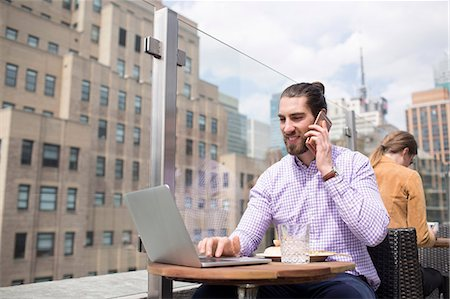 restaurant new york manhattan - Businessman talking on phone while using laptop at rooftop restaurant Stock Photo - Premium Royalty-Free, Code: 6127-08704362