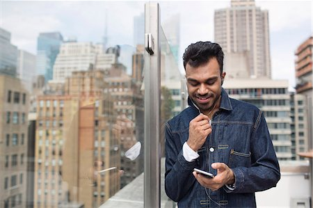restaurant new york manhattan - Happy man text messaging while standing by glass window at rooftop restaurant Stock Photo - Premium Royalty-Free, Code: 6127-08704367