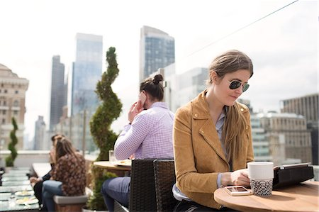restaurant new york manhattan - Businesswoman using digital tablet while people working in background Stock Photo - Premium Royalty-Free, Code: 6127-08704364