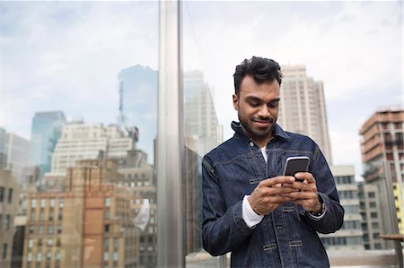 restaurant new york manhattan - Smiling young man using phone while standing by window at rooftop restaurant Stock Photo - Premium Royalty-Free, Code: 6127-08704366