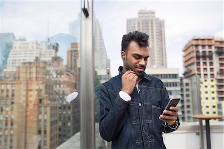 restaurant new york manhattan - Man using phone while standing by glass window at rooftop restaurant Stock Photo - Premium Royalty-Free, Code: 6127-08704368