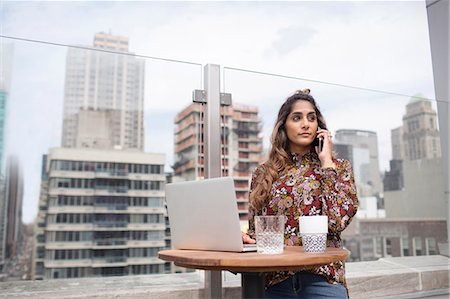 restaurant new york manhattan - Confident woman using phone and laptop while standing at rooftop restaurant Stock Photo - Premium Royalty-Free, Code: 6127-08704369
