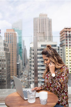 restaurant new york manhattan - Smiling woman working with laptop at rooftop restaurant Stock Photo - Premium Royalty-Free, Code: 6127-08704371