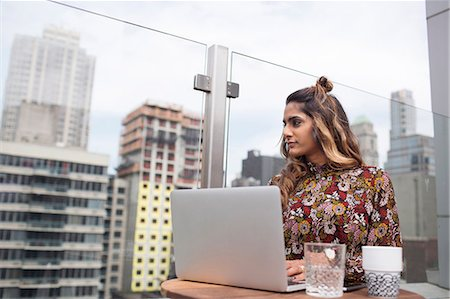 restaurant new york manhattan - Thoughtful woman using laptop while standing at rooftop restaurant Stock Photo - Premium Royalty-Free, Code: 6127-08704372