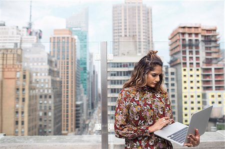 restaurant new york manhattan - Woman looking at laptop while standing against glass window Stock Photo - Premium Royalty-Free, Code: 6127-08704376