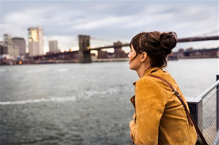 Side view of woman looking at East River while standing against Brooklyn bridge Stock Photo - Premium Royalty-Free, Code: 6127-08704397