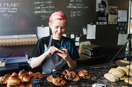 europe coffee shop - Smiling owner photographing breads in coffee shop Stock Photo - Premium Royalty-Free, Code: 6127-08704665