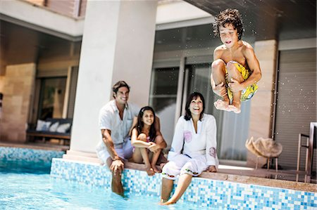 Young boy cannonballs into a pool while his smiling family watch. Stock Photo - Premium Royalty-Free, Code: 6128-08747483