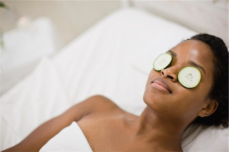 Young woman lying on her back in bed with cucumber slices over her eyes. Stock Photo - Premium Royalty-Free, Code: 6128-08747580